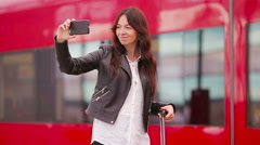 Young woman with luggage taking selfie at a train station. Caucasiam tourist Stock Footage
