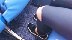 Young woman constrained on the plane. She stretches out her legs, so a bit of Stock Footage