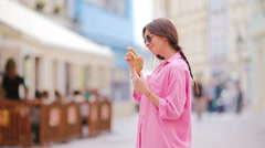 Young female model eating ice cream cone outdoors. Summer concept - woamn with Stock Footage