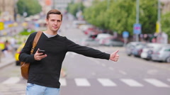 Young happy man catch a taxi in european streets. Portrait of a caucasian - stock footage