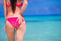 Sexy back of beautiful woman in red bikini on sea background - stock photo