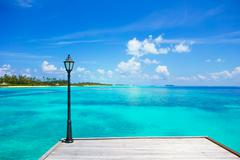 Lantern on the bridge at wooden pier with turquoise water at ideal island - stock photo