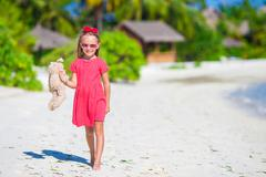 Adorable little girl playing with plush toy on beach Stock Photos