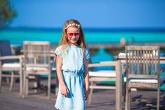 Adorable little girl at outdoor cafe during summer vacation Stock Photos