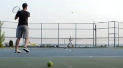 Man and girl playing tennis Stock Footage