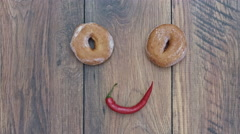 4k Donuts Composition on a Wooden Background with Chilli Face Stock Footage