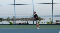 Men playing tennis on a sunny day Stock Footage