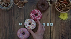 4k Donuts Composition on a Wooden Background with a hand adding one - stock footage