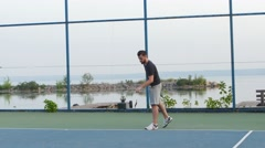 Man practicing his tennis skills at an outdoor court Stock Footage