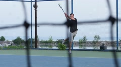 Tennis concept. Player expecting the tennis ball on court, net in front Stock Footage