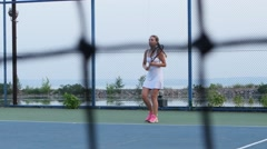 On the tennis court - personal trainer training a tennis player. Net in front Stock Footage