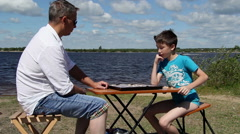 Father and son playing chess outdoors. Stock Footage