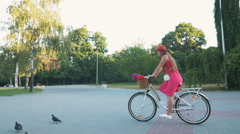 Young attractive girl riding on vintage bike in park at the morning, slow motion Stock Footage