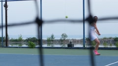 Woman hitting tennis ball with racquet Stock Footage