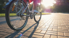 Close up shot of young girl riding on vintage bike in park at sunrise Stock Footage