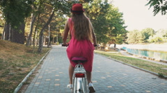 Young attractive girl riding on vintage bike in park at sunset, slow motion Stock Footage