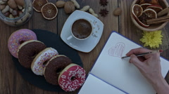 4k Donuts Composition on a Wooden Background with a Hand drawing a Heart Stock Footage