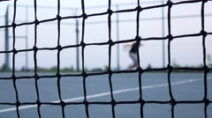 Tennis player volleys using forehand technique. Tennis net in front. Dolly shot Stock Footage