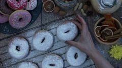 4k Donuts Composition on a Wooden Background with a Hand Putting one Stock Footage