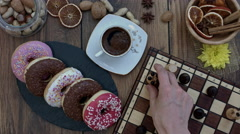 4k Donuts Composition on a Wooden Background with Chess Board Stock Footage