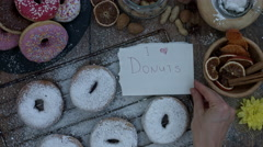 4k Donuts Composition on a Wooden Background with Paper: I love Donuts Stock Footage