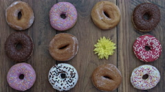 4k Donuts Composition on a Wooden Background with a hand putting Flower Stock Footage