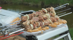 Man takes the skewers with fresh meat for roasting - stock footage