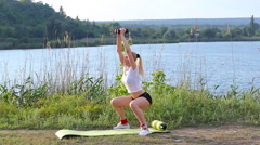 Athlete female squats weighted arm legs workout outdors Stock Footage
