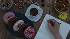 4k Donuts Composition on a Wooden Background with a Hans writing Diet Stock Footage