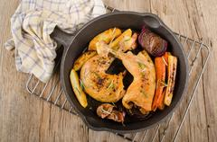 grilled chicken drumsticks with vegetable in a cast iron pan - stock photo
