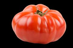 One big beef tomato on black background Stock Photos