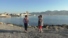 Three Women Are Standing on Pebble Beach on Background of Coastline and Stock Footage