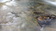 Rocks in stream with smooth flowing water Stock Footage