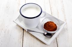 Cold milk in a enamel cup and cocoa in a glass bowl Stock Photos