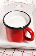 Warm milk in a red enamel mug Stock Photos