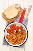 Crackling with cherry tomato in a pan Stock Photos