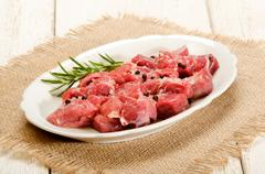 Preparation of raw deer goulash with rosemary, peppercorn Stock Photos