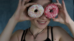 4k Shot of a Woman Posing in Studio with Donuts on Eyes Stock Footage