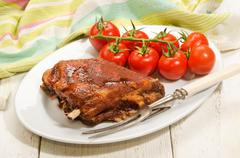 Crispy marinated ribs and fresh tomatoes on an oval plate Stock Photos