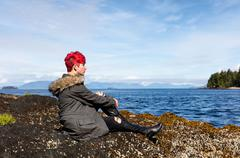 Teen girl thinking while sitting on rock near lake and woods - stock photo