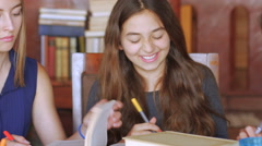 Three beautiful young women learn with books and technology together - stock footage