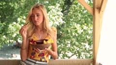 Sexy smiling woman eating vegetable at the beach - stock footage