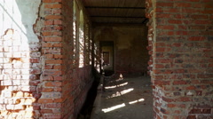 View through doorway into narrow hallway with sunlit patch on bare stone wall. Stock Footage