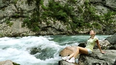 Girl sits on the bank of the rapid river clean.  Woman and mountain river. Stock Footage