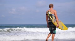 Active Young Surfer with Surfboard Walking at Beach Stock Footage