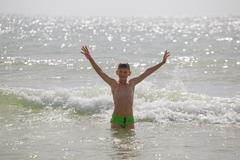 Picture of exciting boy running on beach beside waves. image of kid in evenin Stock Photos