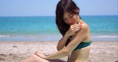 Smiling woman applying suntan lotion on a beach Stock Footage