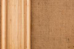 Bamboo mat twisted in the form of a manuscript on sackcloth - stock photo
