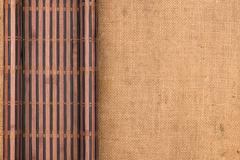 Bamboo mat twisted in the form of a manuscript on sackcloth Stock Photos