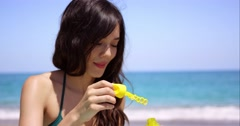 Young woman blowing soapy iridescent bubbles Stock Footage